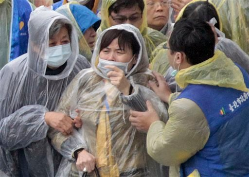 Relatives from mainland China react as they watch divers recover bodies at the site of a commercial plane crash in Taipei, Taiwan, Friday, Feb. 6, 2015. TransAsia Airways Flight 235 clipped a bridge shortly after takeoff and crashed into a river in the is