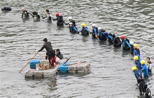 Search and rescue divers continue to search for missing persons at the site of a commercial plane crash in Taipei, Taiwan, Friday, Feb. 6, 2015. TransAsia Airways Flight 235, with 58 people aboard, clipped a bridge shortly after takeoff and crashed into a
