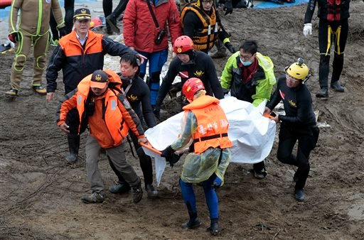 Search and rescue divers carry a recovered body at the site of a commercial plane crash in Taipei, Taiwan, Friday, Feb. 6, 2015. TransAsia Airways Flight 235 with 58 people aboard clipped a bridge shortly after takeoff and crashed into a river in the isla
