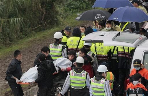Relatives from mainland China watch bodies being recovered at the site of a commercial plane crash in Taipei, Taiwan, Friday, Feb. 6, 2015. TransAsia Airways Flight 235 with 58 people aboard clipped a bridge shortly after takeoff and crashed into a river