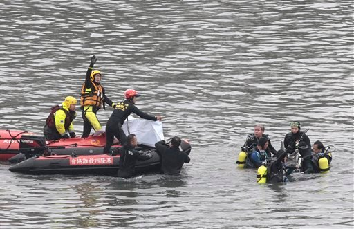 Search and rescue divers signal as they recover two bodies at the site of a commercial plane crash in Taipei, Taiwan, Friday, Feb. 6, 2015. TransAsia Airways Flight 235 with 58 people aboard clipped a bridge shortly after takeoff and crashed into a river