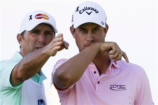 Harris English, right, speaks with his caddie, Brian Smith, before hitting his tee shot on the 18th hole of the north course during the second round of the Farmers Insurance Open golf tournament Friday, Feb. 6, 2015, in San Diego. (AP Photo/Gregory Bull)