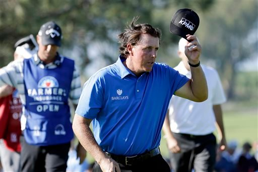 Phil Mickelson, right, tips his hat after finishing on the ninth hole of the north course during the second round of the Farmers Insurance Open golf tournament Friday, Feb. 6, 2015, in San Diego. (AP Photo/Gregory Bull)