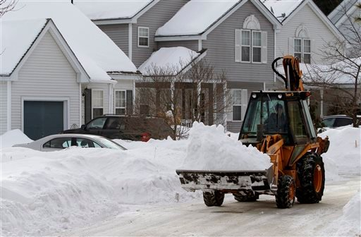 A worker uses a front-end loader to remove piled snow Saturday, Feb. 7, 2015, from a street in Marlborough, Mass. A long duration winter storm was forecast to begin Saturday night and remain in effect for a large swath of southern New England until the ea