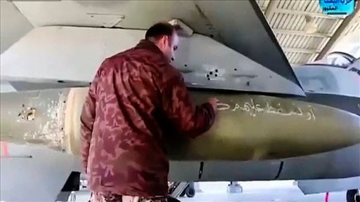 In this image made from Wednesday, Feb. 4, 2015, video provided by Jordanian military via Roya TV, an air force pilot writes a message to Islamic State militants on a missile at Mowafak Al-Salti airbase in Azraq, Jordan. The military carried out airstrike