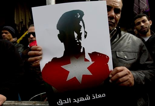 """A Jordanian demonstrator carries a poster with a picture of slain Jordanian pilot, Lt. Muath al-Kaseasbeh, and Arabic that reads, """"Muath is the martyr of the right,"""" during an anti-IS group rally in Amman, Jordan, Friday, Feb. 6, 2015. Several thousand pe"""