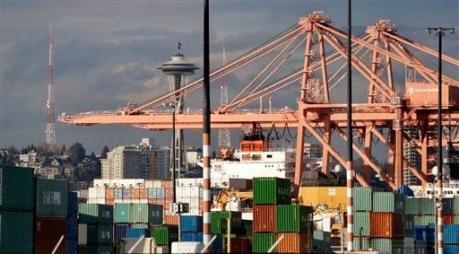 The Space Needle in seen in view of cranes, containers and container ships at the Port of Seattle Friday, Feb. 6, 2015, in Seattle. Companies that handle billions of dollars of cargo at West Coast seaports said they will hire far fewer workers this weeken
