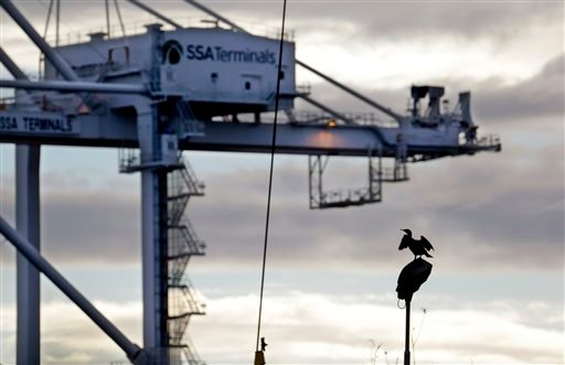 A cormorant spreads its wings to dry while sitting on a light fixture in view of a container crane at the Port of Seattle Friday, Feb. 6, 2015, in Seattle. Companies that handle billions of dollars of cargo at West Coast seaports said they will hire far f