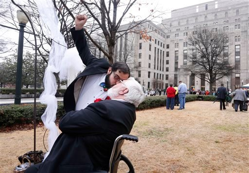 Eli Wright raises his fist as he kisses his partner Don Wright, having just been married in Linn Park, at the Jefferson County Courthouse, Monday, Feb. 9, 2015, in Birmingham, Ala. A federal judge's order overturning the state's ban on gay marriage goes i