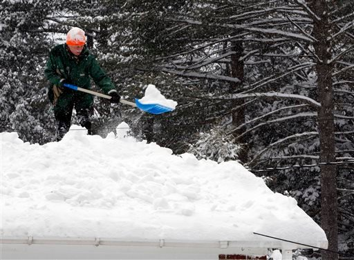 Bjorn Lange works to shovel off his roof as another snowstorm hits the area Monday, Feb. 9, 2015, in Concord, N.H. More light, fluffy snow was falling in much of New Hampshire on Monday. (AP Photo/Jim Cole)
