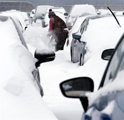 Mary Mulloy, of Strafford, Vt., works to dig her car out of the long term parking lot at the airport, Monday, Feb. 9, 2015, in Manchester, N.H. Mulloy was returning from Salt Lake City, where temperatures were in the 70s. (AP Photo/Jim Cole)