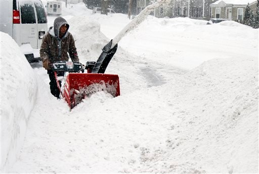 Mauricio Siba clears snow from a driveway Feb. 9, 2015, in Framingham, Mass. A long duration winter storm that began Saturday night remains in effect for a large swath of southern New England until the early Tuesday. (AP Photo/Bill Sikes)