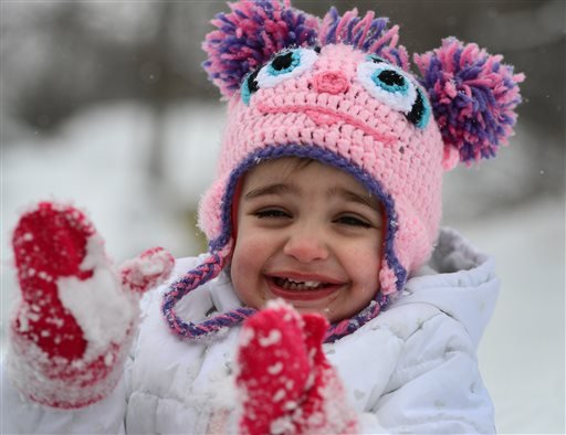 Abigail Deep claps her hands to get the snow off her mittens, Monday, Feb. 9, 2015, in Utica, N.Y. The third major winter storm in less than two weeks inflicted fresh snow across New England and portions of New York state on Monday. (AP Photo/Observer-Dis
