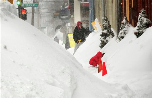 Snow is piled high along the business area of State Street, Monday, Feb. 9, 2015, in Newburyport, Mass. A long duration winter storm that began Saturday night remains in effect for a large swath of southern New England until the early morning hours Tuesda