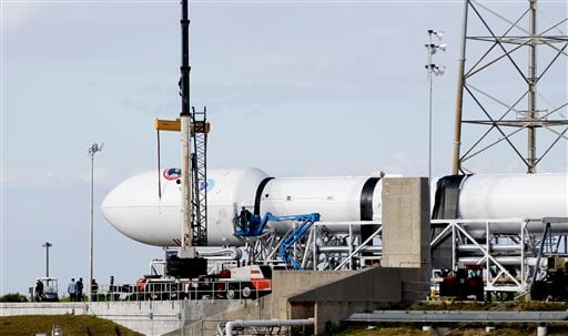 Maintenance is performed by workers on the Falcon 9 SpaceX rocket at launch complex 40 at the Cape Canaveral Air Force Station in Cape Canaveral, Fla., Monday, Feb. 9, 2015. The Sunday launch attempt was scrubbed and SpaceX will try again on Tuesday eveni