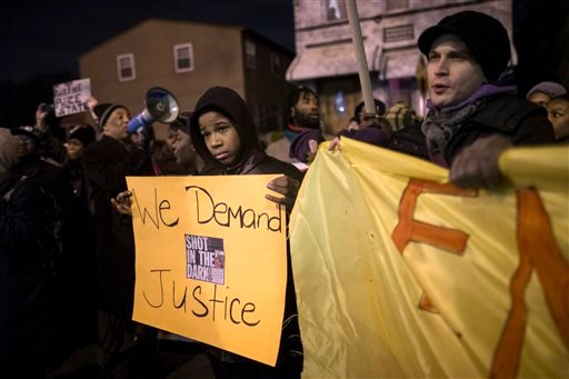 FILE - In this Nov. 22, 2014, file photo, demonstrators pause outside the 75th Police Precinct during a march in protest of the shooting death of Akai Gurley by rookie NYPD officer Peter Liang at the Louis Pink Houses public housing complex in New York.