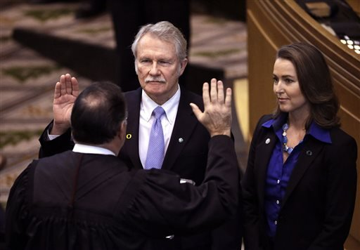FILE - In this Jan. 12, 2015 file photo, Oregon Gov. John Kitzhaber, middle, is joined by his fiancee, Cylvia Hayes, as he is sworn in for an unprecedented fourth term by Senior Judge Paul J. De Muniz in Salem, Ore. (AP)