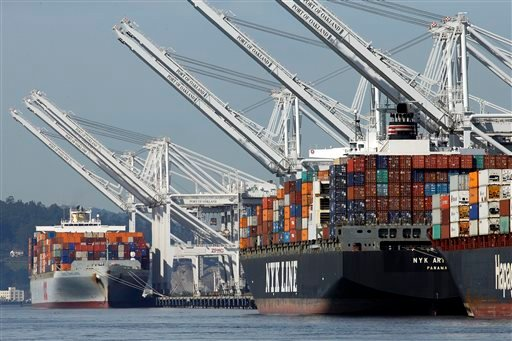 Container ships wait at the dock to be unloaded at the Port of Oakland Thursday, Feb. 12, 2015, in Oakland, Calif. Companies that operate marine terminals didn't call workers to unload ships Thursday that carry car parts, furniture, clothing, electronics,