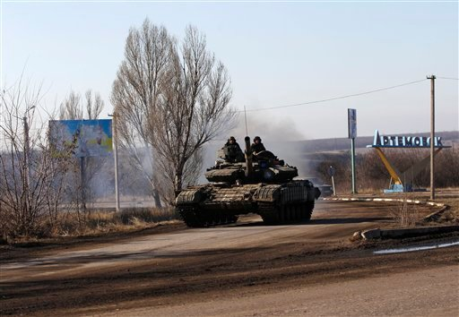 Ukrainian government troops ride a tank on a road towards Debaltseve near the town of Artemivsk, Ukraine, Friday, Feb. 13, 2015. The fighting between Russia-backed separatists and Ukrainian government forces has continued despite the agreement reached by