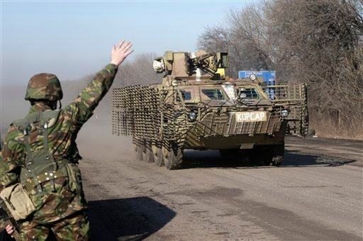A Ukrainian government troop waves to a armored vehicle driving on the road towards Debaltseve near the town of Artemivsk, Ukraine, Friday, Feb. 13, 2015. The fighting between Russia-backed separatists and Ukrainian government forces has continued despite
