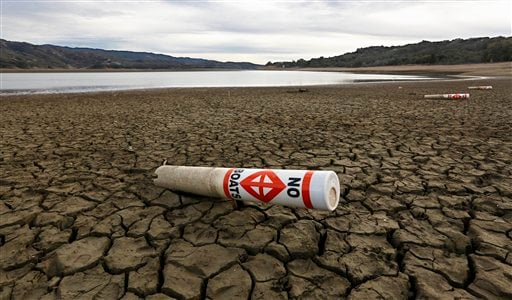 In this Feb. 4 2014 file photo, a warning buoy sits on the dry, cracked bed of Lake Mendocino near Ukiah, Calif. (AP Photo/Rich Pedroncelli, File)