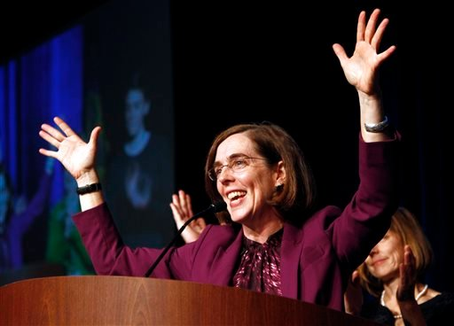 In this Nov. 6, 2012 file photo, Oregon Democratic Secretary of State Kate Brown celebrates at the podium after winning her race at Democratic headquarters in Portland, Ore. Brown, a fellow Democrat, is widely considered to be to the left of Gov. John Kit