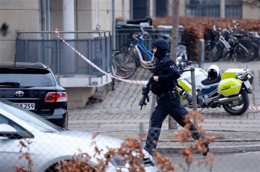 "An armed security officer runs down a street near a venue after shots were fired where an event titled ""Art, blasphemy and the freedom of expression"" was being held in Copenhagen, Saturday, Feb. 14, 2015. Danish media say several shots have been fired at"