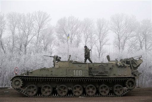 Ukrainian government soldier walks atop of his armored vehicle on the road between the towns of Dabeltseve and Artemivsk, Ukraine, Sunday, Feb. 15, 2015. International attention will be focused in the coming days on the strategic railway hub of Debaltseve