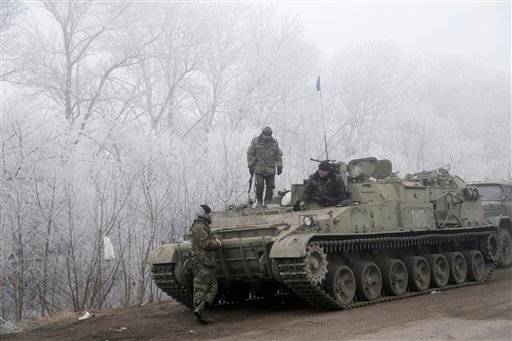 Ukrainian government soldiers rest by armored vehicle on the road between the towns of Dabeltseve and Artemivsk, Ukraine, Sunday, Feb. 15, 2015. International attention will be focused in the coming days on the strategic railway hub of Debaltseve, where U