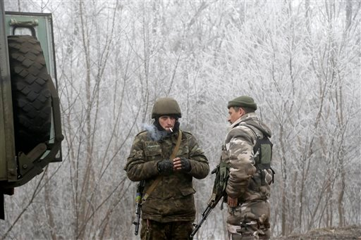 Ukrainian government soldiers take a rest on the road between the towns of Dabeltseve and Artemivsk, Ukraine, Sunday, Feb. 15, 2015. International attention will be focused in the coming days on the strategic railway hub of Debaltseve, where Ukrainian gov