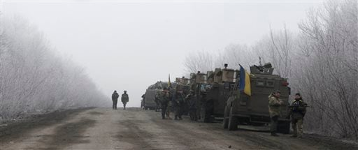 Ukrainian military convoy stop on the road between the towns of Dabeltseve and Artemivsk, Ukraine, Saturday, Feb. 14, 2015. The fighting between Russia-backed separatists and Ukrainian government forces has continued despite the agreement reached by leade