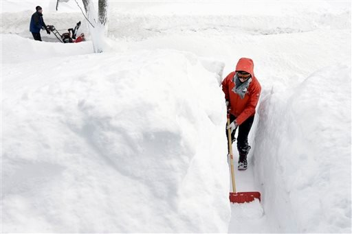 Kim Taylor, of Norwood, Mass., right, shovels a path in the snow in front of her home Sunday, Feb. 15, 2015, in Norwood. A storm brought a new round of wind-whipped snow to New England on Sunday, threatening white-out conditions in coastal areas and forci