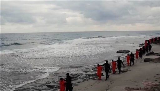 This image made from a video released Sunday Feb. 15, 2015 by militants in Libya claiming loyalty to the Islamic State group purportedly shows Egyptian Coptic Christians in orange jumpsuits being led along a beach, each accompanied by a masked militant. L