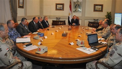 In this image released by the Egyptian Presidency in the early hours of Monday, Feb. 16, 2015, President Abdel-Fattah el-Sissi, center, meets with cabinet officials and military officers after militants in Libya affiliated with the Islamic State group rel