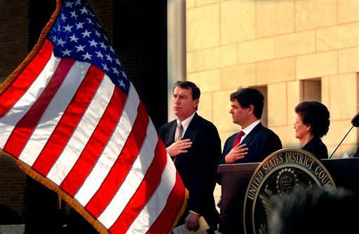 In this Nov. 14, 2005, file photo, U.S. Southern District Judge Andrew S. Hanen, left, joins with Filemon B. Vela, Jr. and Blanca Vela for the Pledge of Allegiance during the United States Courthouse naming ceremony in Brownsville, Texas. Hanen temporari