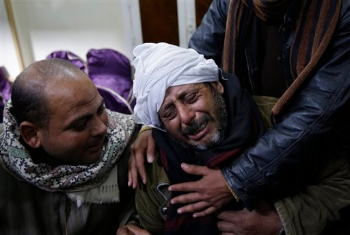 A man is comforted by others as he mourns over Egyptian Coptic Christians who were captured in Libya and killed by militants affiliated with the Islamic State group, outside of the Virgin Mary church in the village of el-Aour, near Minya, 220 kilometers (