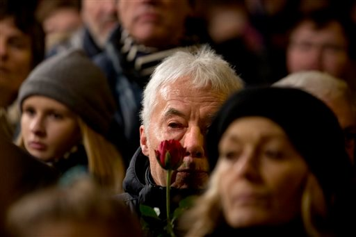 People are gather during a vigil in honor of the two men killed by a gunman over the weekend, at Oesterbro, near the Teater Building 'Krudttonden', the scene of the first attack, Monday, Feb. 16, 2015 in Copenhagen Denmark. (AP Photo/Polfoto, Finn Frandse