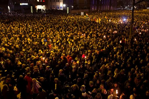People gather during a memorial service in honor of the two men killed killed by a gunman over the weekend, at Oesterbro, near the Teater Building 'Krudttonden', the scene of the first attack, Monday evening, Feb. 16, 2015 in Copenhagen Denmark. (AP Photo