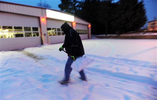 Tevin Doughty shovels snow at the Community Fire Company, Inc., Tuesday, Feb. 17, 2015, in Exmore, Va. A snow and ice storm blasted parts of the Mid-Atlantic and the South on Tuesday, creating treacherous road conditions and leaving hundreds of thousands