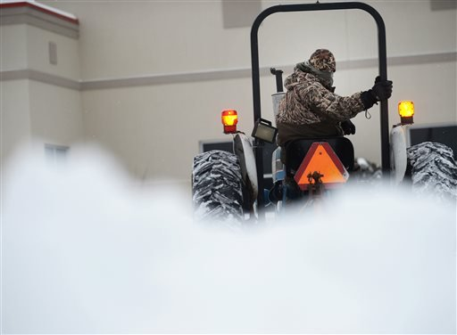 Duane Read clears snow at the Eastern Shore Family YMCA, Tuesday, Feb. 17, 2015, in Onley, Va. A snow and ice storm blasted parts of the Mid-Atlantic and the South on Tuesday, creating treacherous road conditions and leaving hundreds of thousands without