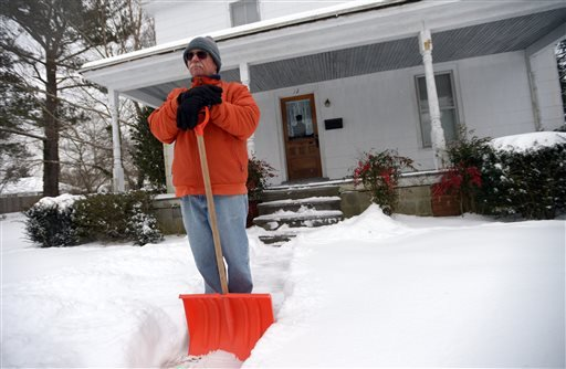 Bob Wessel takes a break from shoveling his sidewalk, Tuesday, Feb. 17, 2015, in Onancock, Va. A snow and ice storm blasted parts of the Mid-Atlantic and the South on Tuesday, creating treacherous road conditions and leaving hundreds of thousands without