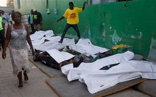 A woman walks away from bodies after failing to find a missing family member among them outside the morgue at the General Hospital in Port-au-Prince, Haiti, Tuesday, Feb. 17, 2015. (AP)