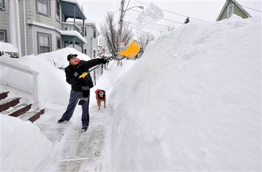 FILE - In this Feb. 10, 2015 file photo, Lee Anderson adds to the pile of snow beside the sidewalk in front of his house in Somerville, Mass., as his dog Ace watches. (AP Photo/Josh Reynolds, File)