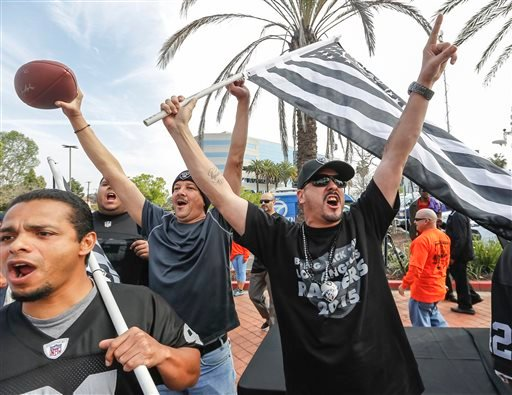 Raiders fan Sergio Gutierrez, right, joins football fans celebrating a proposed NFL football stadium by the owners of the San Diego Chargers and Oakland Raiders, during a news conference in Carson, Calif., on Friday, Feb. 20, 2015.