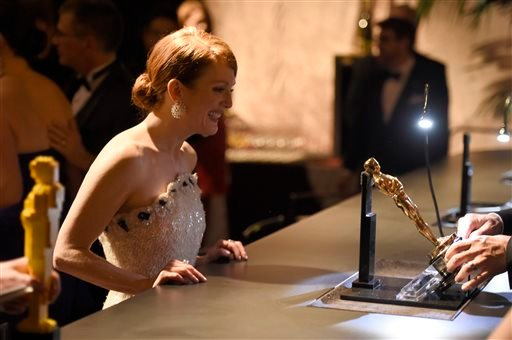 "Julianne Moore, winner of the award for best actress in a leading role for ""Still Alice"", waits for her Oscar to be engraved at the Governors Ball after the Oscars on Sunday, Feb. 22, 2015, in Los Angeles. (Photo by Chris Pizzello/Invision/AP)"