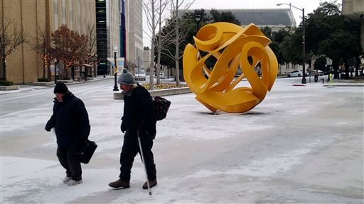 Donna Newton and Michael Moore make their way past the Tabachin Ribbon sculpture as they leave municipal court Monday, Feb. 23, 2015, in Fort Worth, Texas. Freezing rain affected travel in nearly half of Texas of Monday, and winter storm warnings were iss