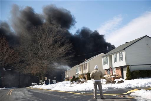 A man looks at heavy black smoke, Monday, Feb. 23, 2015, in Pennsauken, N.J. Authorities say a tanker truck carrying nearly 9,000 gallons of fuel has caught fire on a major southern New Jersey highway. (AP Photo/Matt Rourke)