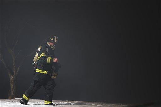 A firefighter is engulfed in smoke from a tanker truck fire Monday, Feb. 23, 2015, in Pennsauken, N.J. The fire broke out shortly after 11 a.m. (AP Photo/Matt Rourke)
