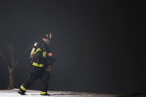 A firefighter is engulfed in smoke from a tanker truck fire Monday, Feb. 23, 2015, in Pennsauken, N.J. The fire broke out shortly after 11 a.m. (AP Photo/Matt Rourke)