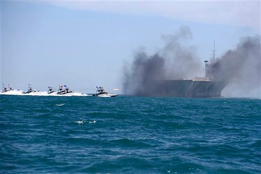 In this picture released by the semi-official Iranian Fars news agency on Wednesday, Feb. 25, 2015, Revolutionary Guard speedboats assault a replica of a U.S. aircraft carrier during large-scale naval drills near the entrance of the Persian Gulf, Iran.